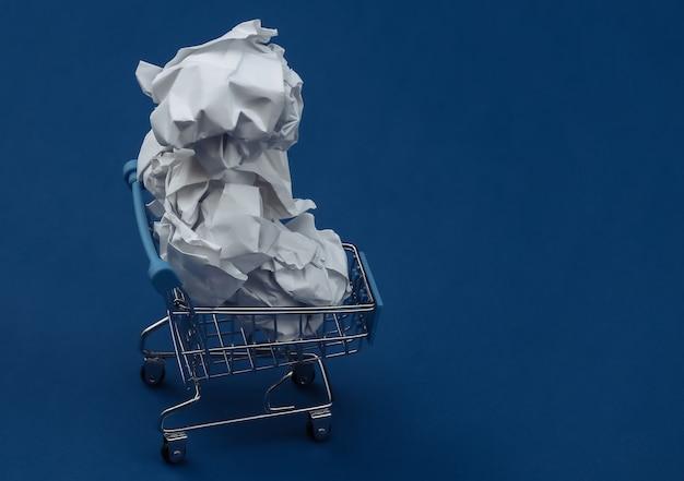 Wózek na zakupy z pomiętymi papierowymi kulkami na klasycznym niebieskim tle. kolor 2020.
