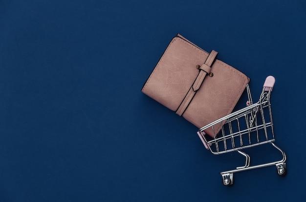 Wózek na zakupy z portfelem na klasycznym niebieskim tle. kolor 2020. widok z góry.
