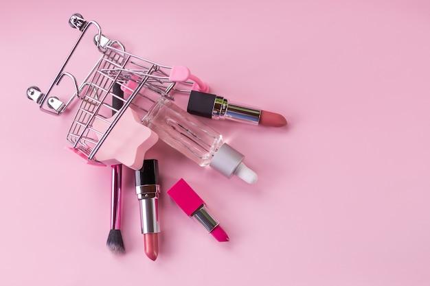 Wózek na zakupy z produktami do makijażu na różowym tle. koszyk z kosmetykami. koncepcja sprzedaży online. kosmetyki do pielęgnacji skóry i szminki. baner reklamowy i marketingowy