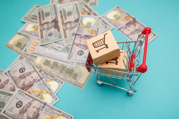 Wózek na zakupy z pudełkami i banknotami dolara na niebiesko.