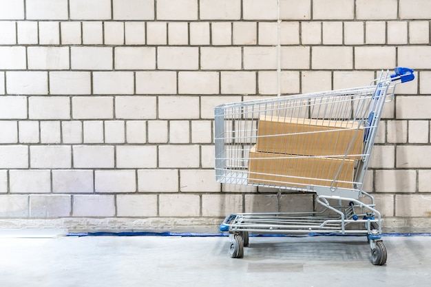 Wózek na zakupy z pudełkami przed ściana z cegieł