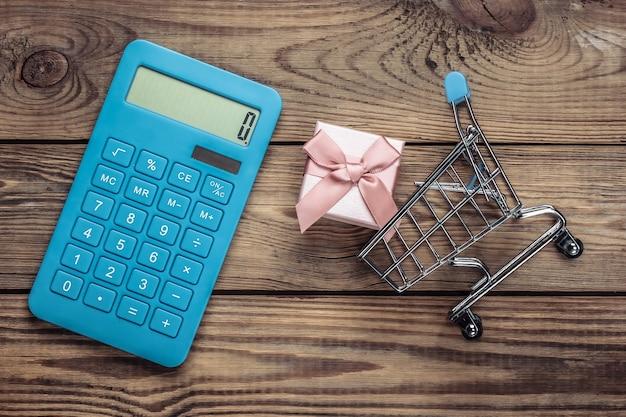Wózek na zakupy z pudełkiem i kalkulatorem na drewnianym stole. kalkulacja kosztów świątecznych zakupów