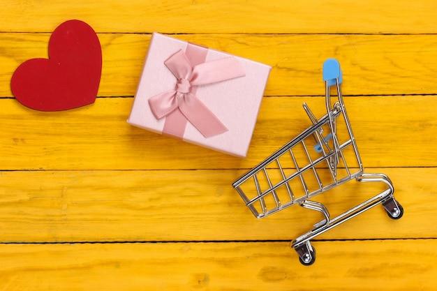 Wózek na zakupy z pudełkiem i sercem na żółtym drewnianym tle