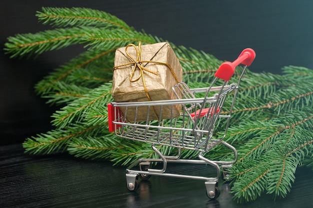 Wózek na zakupy z pudełkiem na prezent i brunchem z drzewa futerkowego. wyprzedaż świąteczna