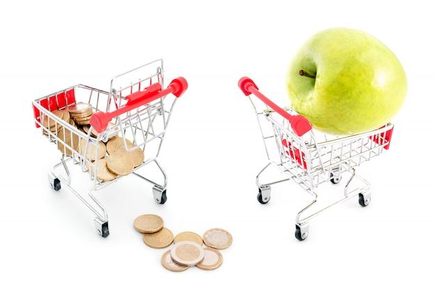 Wózek na zakupy z spadającymi od niego monetami euro na białym tle i zielonym jabłku. sprzedaż, obfitość, zbiory, zakupy w supermarketach, sprzedaż i motyw zwrotu gotówki.