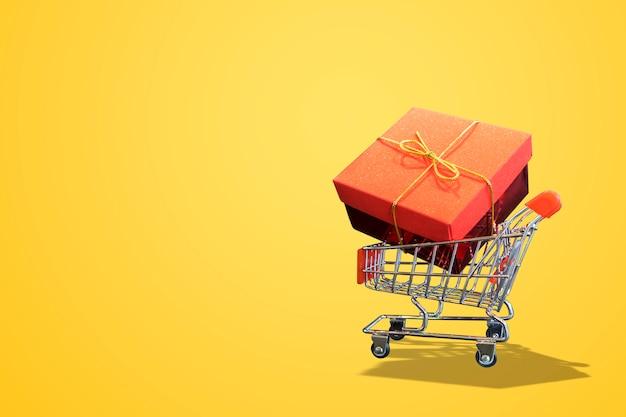 Wózek na zakupy żółty tło i prezenta pudełko