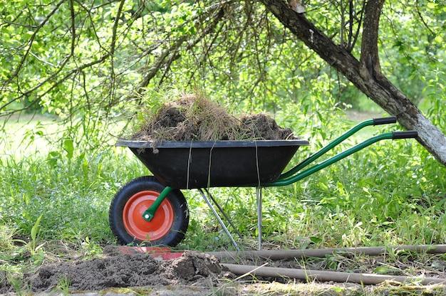 Wózek ogrodowy z ziemią w ogrodzie