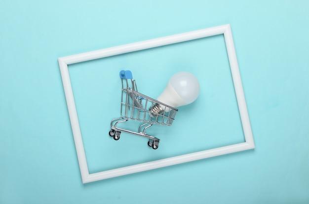 Wózek sklepowy i żarówka led na niebieskiej powierzchni z białą ramką