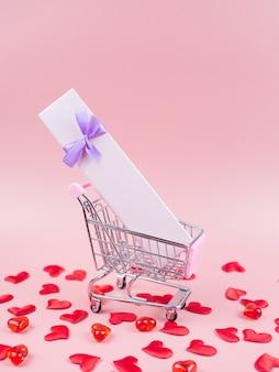 Wózek sklepowy w pudełku prezentowym, czerwone serca. walentynki zakupy koncepcja