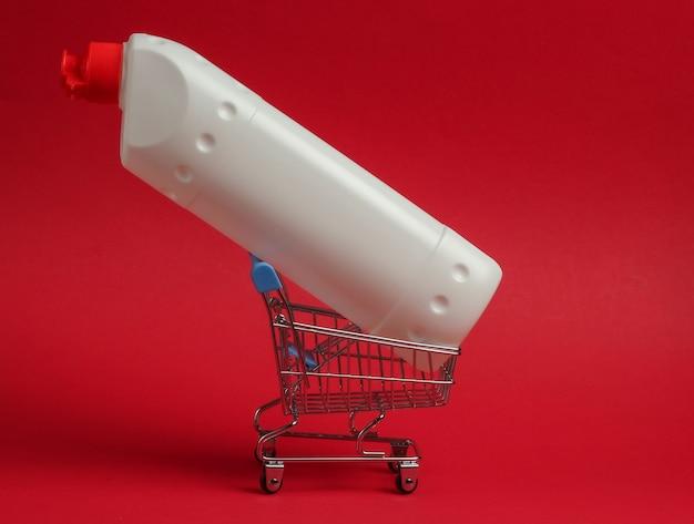 Wózek sklepowy z białą plastikową butelką detergentu do łazienki i toalety na czerwonym tle.