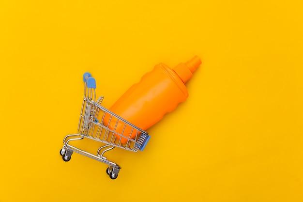 Wózek sklepowy z butelką z filtrem przeciwsłonecznym w kolorze żółtym ochrona skóry. wakacje na plaży