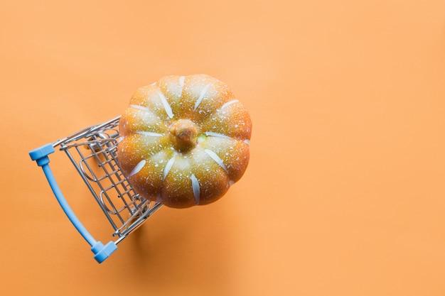 Wózek sklepowy z dynią na pomarańczowo.
