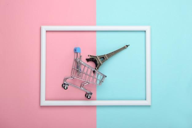 Wózek sklepowy z figurką wieży eiffla w białej ramie na różowo-niebieskiej powierzchni