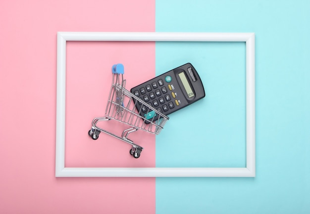 Wózek sklepowy z kalkulatorem w białej ramce na różowo-niebieskiej pastelowej powierzchni