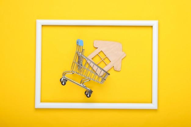 Wózek sklepowy z mini domkiem w białej ramie na żółtej powierzchni