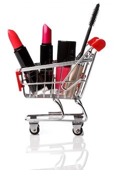 Wózek sklepowy z produktami do makijażu w środku