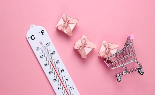 Wózek sklepowy z pudełkami na prezenty i termometrem pogodowym na różowym pastelowym kolorze