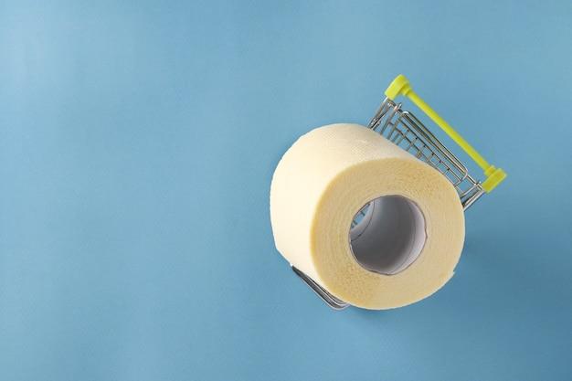 Wózek sklepowy z rolką miękkiego papieru toaletowego na niebieskim tle, pandemia covid-19, zwiększone nieoczekiwane zapotrzebowanie, miejsce do kopiowania