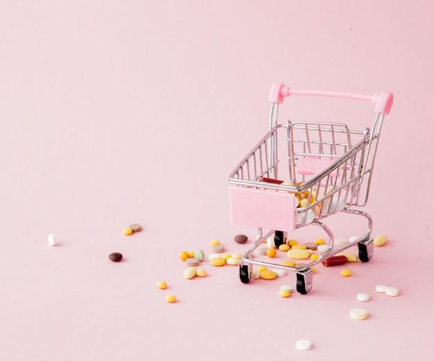 Wózek sklepowy z supermarketu pełen tabletek i leków na różowym stole. zakupy preparatów medycznych, zakup przez internet. leżał płasko, widok z góry