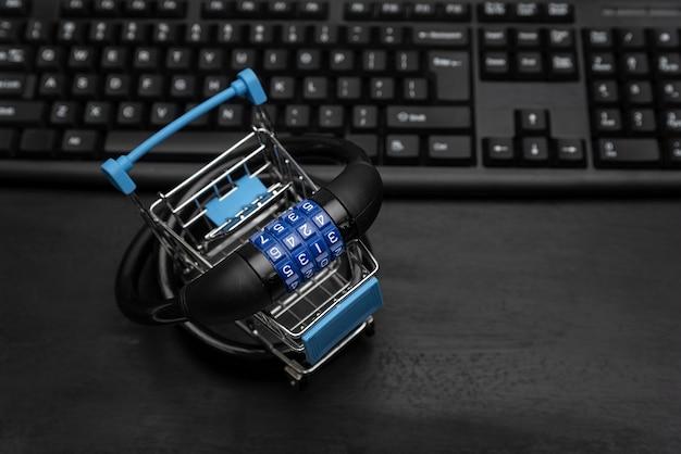 Wózek sklepowy z zamkiem szyfrowym, klawiaturą komputerową na powierzchni. bezpieczeństwo zakupów online.