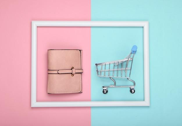 Wózek sklepowy ze skórzanym portfelem w białej ramie na różowo-niebieskiej pastelowej powierzchni