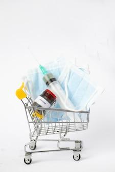 Wózek spożywczy z artykułami medycznymi. wózek z maseczkami medycznymi, zastrzykiem i szczepionką pandemiczną. covid-19. apteka. zakup leków
