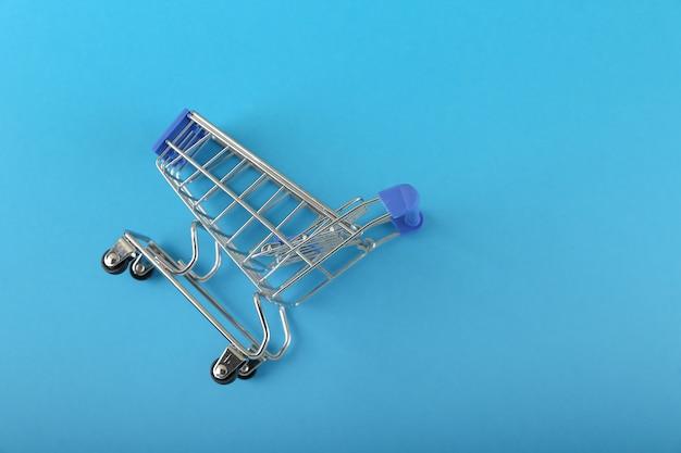 Wózek supermarket jest na niebieskim tle z miejsca na kopię