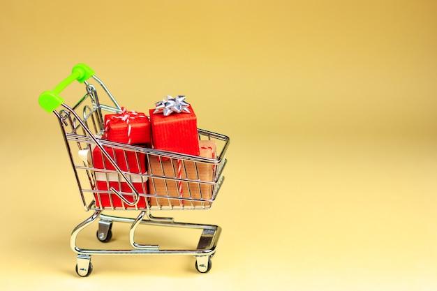 Wózek supermarketowy pełen prezentów na żółto