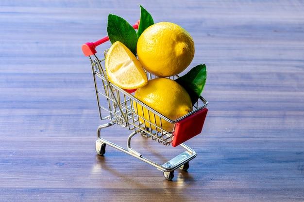 Wózek supermarketowy z zielonym liściem i cytryną