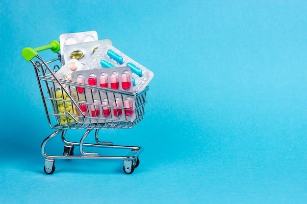 Wózek supermarketu pełen materiałów medycznych. tabletki w blistrach