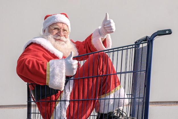 Wózek supermarketu z mikołajem w środku. kciuk w górę. zakupy na boże narodzenie koncepcja.