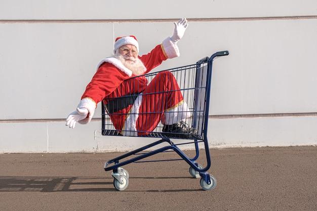 Wózek supermarketu z mikołajem w środku. zakupy na boże narodzenie koncepcja.