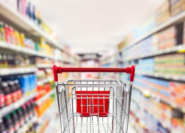 Wózek transportowy w niewyraźne wnętrze supermarketu dla koncepcji biznesowej