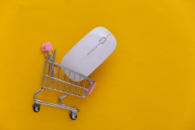 Wózek w supermarkecie z myszką komputerową na żółtym tle. zakupy online. widok z góry
