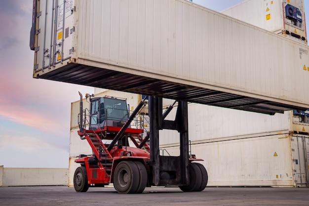 Wózek widłowy ładuje białą skrzynię kontenerową do logistycznego importu, eksportu i branży transportowej. transport ciężarowy ładunków w doku statku towarowego z dźwigiem przemysłowym.