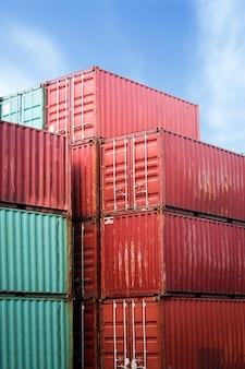 Wózek widłowy podnoszący kontener ładunkowy w stoczni wysyłkowej lub stoczni dokowej przed wschodem słońca nieba ze stosem kontenerów w tle do importu, eksportu i logistyki transportu przemysłowego