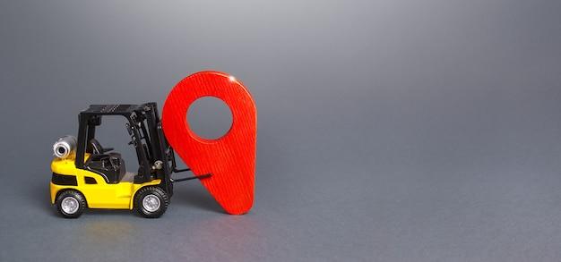 Wózek widłowy ustawia czerwony wskaźnik lokalizacji pinezki. dostawa i dystrybucja towarów