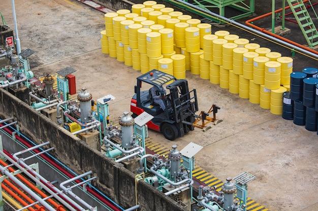 Wózek widłowy z beczkami na olej z widokiem z góry porusza się na ciężarówce transportowej.