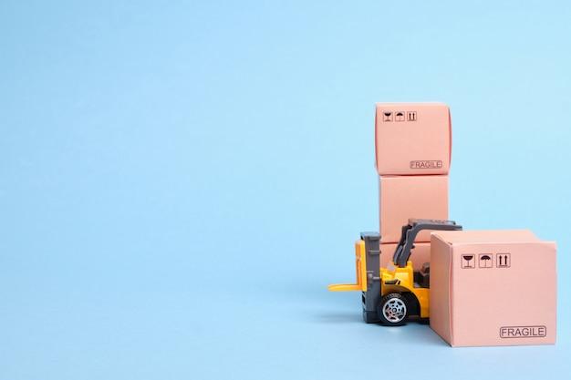 Wózek widłowy z towarami zapakowanymi w pudełka do wysyłania miejsca na kopię.