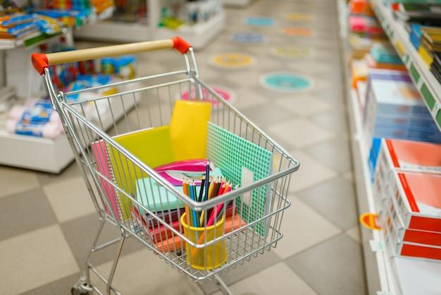 Wózek z artykułami biurowymi między półkami w sklepie papierniczym