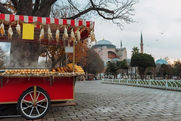 Wózek z grillowaną kukurydzą w muzeum hagia sophia w stambule. azjatycki uliczny jedzenie, istanbuł, turcja