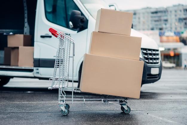 Wózek z kartonami przeciwko ciężarówce. dystrybucja. dostawa ładunków. puste, przezroczyste pojemniki. usługi logistyczne i pocztowe