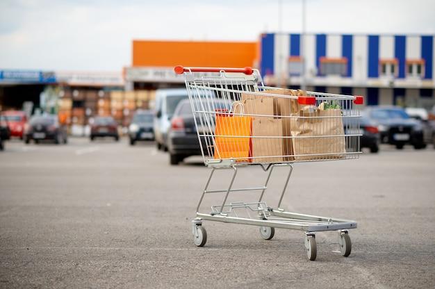 Wózek z kartonowymi torbami na parkingu w supermarkecie
