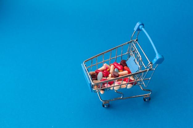 Wózek z supermarketu wypełniony kolorowymi pigułkami