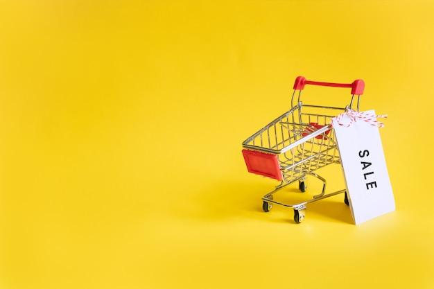 Wózek z zabawkami w supermarkecie z naklejką sprzedaży na żółtym. wyprzedaże, zakupy i czarny piątek. copyspace dla tekstu.