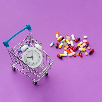 Wózek z zabawkami z zegarem i pigułkami obok