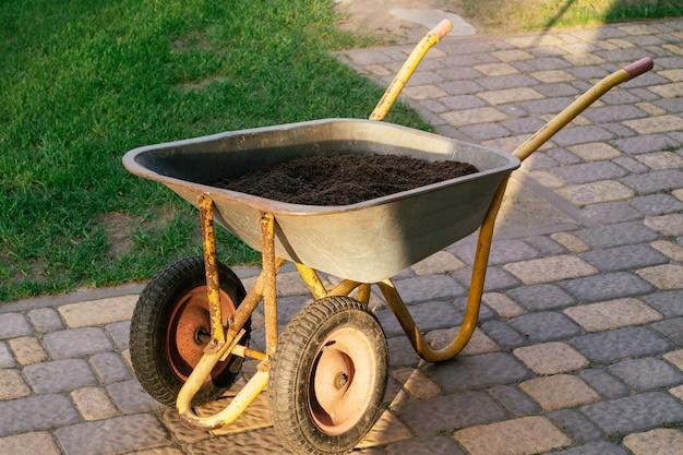 Wózek z ziemią na płytach chodnikowych obok zielonego trawnika. taczka z ziemią, do ogrodnictwa