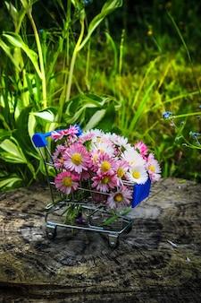 Wózek ze sklepu latem niesie bukiet kwiatów na drewnianym tle