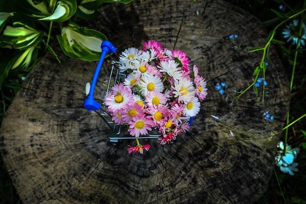 Wózek ze sklepu latem niesie bukiet kwiatów, widok z góry