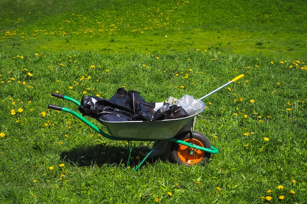Wózek ze śmieciami na zielonej trawie. czyszczenie parku po grillowaniu w przyrodzie.